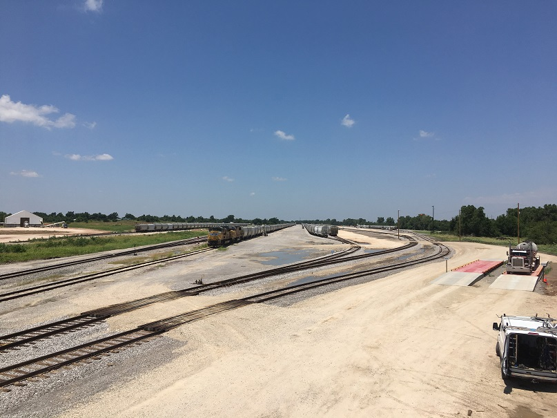 Trucks and trains are positioned to move frac sand at the new Loup railport in El Reno, Oklahoma.